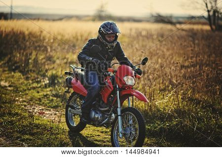 Enduro racer sitting on his red motorcycle