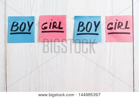 Colorful stickers with boy and girl text, copy space. Composition of pink and blue papers on white wooden background. It's a girl and boy twins concept