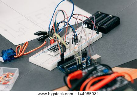 Electronic construction with wiring diagram. Modern engineering creation on gray table, breadboard with colorful cables close up
