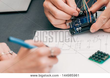 Woman recapping electronics creation process. Engineer assistant drawing wiring diagram of electronic construction. Modern technologies, innovation, diy laboratory