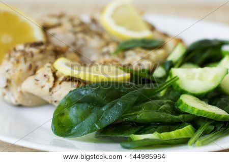 Spinach salad served with baked chicken meat and lemon slices. Healthy eating concept. Low calories diet concept
