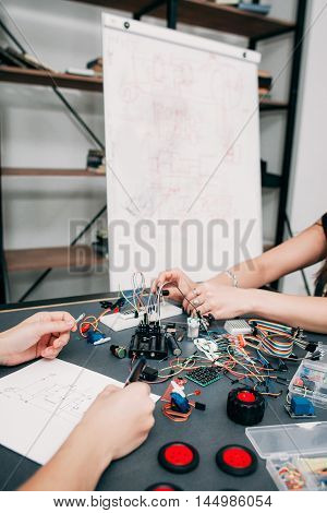 Educational experiment on physics, electronics development. Students connecting electrical components according to wiring diagram on whiteboard to get concrete construction
