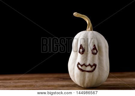 small decorative pumpkin isolated on wood with chocolate face