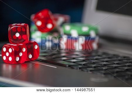 Gambling chips, red dice on laptop keyboard background