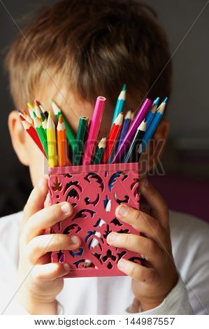 Colored pencils in children's hands, sharpened . Macro