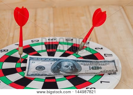 Dart arrow hitting in bullseye on dartboard with money
