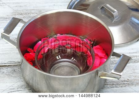 Homemade production of rose water in a way of home distillation from rose petals, a lid is turned upside down on the pot