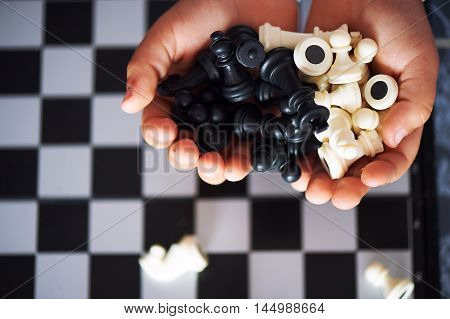 Little baby hands holding the figures of chess. Macro