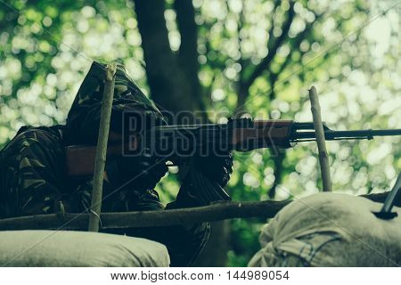 Sniper soldier in military camouflage hood black gloves with gun aiming target in forest on green tree background