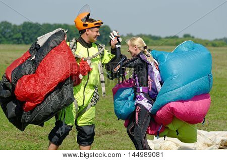Kharkiv Ukraine - August 20 2016: Two skydivers carries a parachute after landing at the airfield Korotych Kharkov region Ukraine on August 20 2016