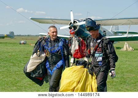 Kharkiv Ukraine - August 20 2016: Three skydivers carries a parachute on background of Antonov An-2 aircraft after landing at the airfield Korotych Kharkov region Ukraine on August 20 2016