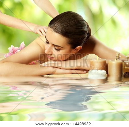 Spa concept. Beautiful woman having massage on table near water. Blurred green foliage background.