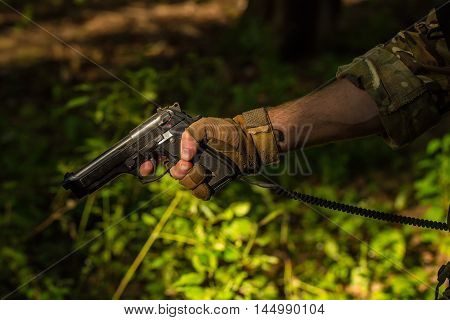 Male hand in military glove with pistol holding finger on firing hammer on green grass background closeup