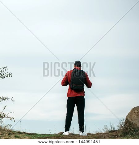 Man standing back in red sports jacket black trousers baseball cap and backpack on blue sky natural background outdoor
