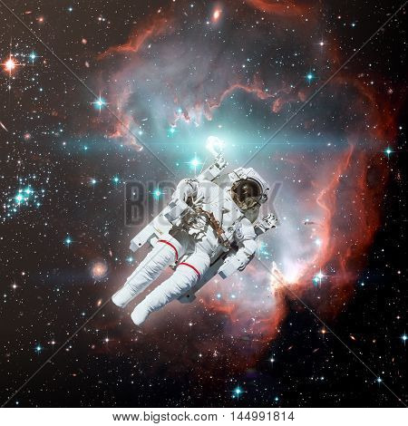 Astronaut in outer space. Nebula on the background. Elements of this image furnished by NASA.
