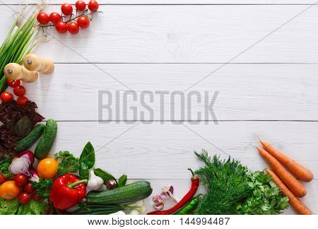 Frame of fresh organic vegetables on white wood background. Healthy natural food on rustic wooden table with copy space. Tomato, lettuce, pepper, zucchini and other cooking ingredients top view