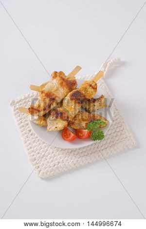 grilled chicken skewers on white plate