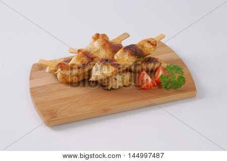 grilled chicken skewers on wooden cutting board