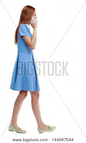 side view of a woman walking with a mobile phone. beautiful girl in motion. Isolated over white background. Skinny girl in blue dress talking while walking on white smartphone.