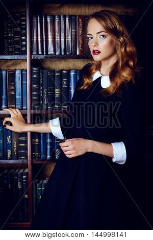 Beautiful young woman wearing old-fashioned  black dress stands in the old library. Retro style. Beauty, fashion.