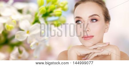 beauty, people and bodycare concept -beautiful young woman face and hands over natural lilac blossom background