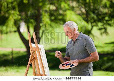 Senior man painting ouside