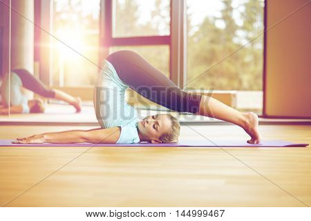 fitness, sport, training and lifestyle concept - smiling woman stretching on mat in gym