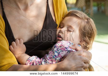 tender scene of two years old child taking nap or sleeping on mother or woman arms