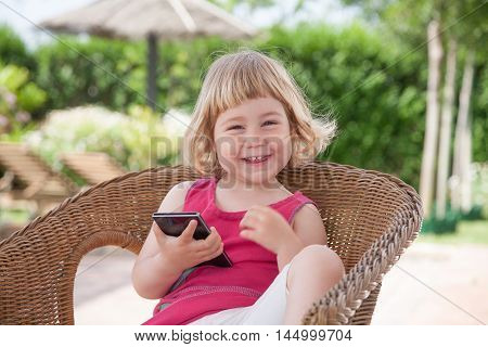 Little Child On Chair With Mobile Looking And Laughing