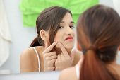 stock photo of pimples  - Young teenage woman with pimple on her face - JPG