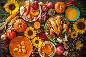 Thanksgiving dinner. Roasted turkey with pumpkins and sunflowers on wooden table poster