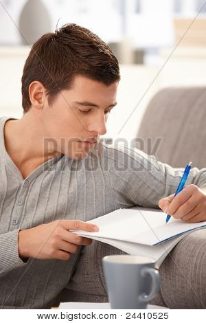 Portrait of college student guy taking notes, studying at home.?