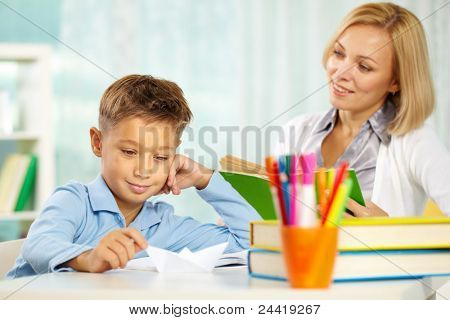 Portrait of handsome boy at workplace with his tutor sitting near by and looking at him