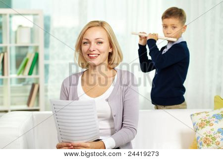 Portrait of happy tutor with notes looking at camera on background of pupil playing the flute