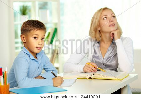 Portrait of diligent boy looking at camera at workplace with his tutor sitting on background