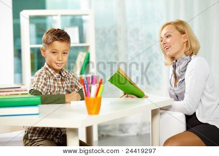 Portrait of diligent boy looking at camera at workplace with his tutor sitting near by