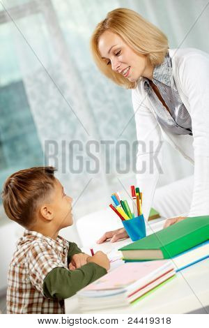 Portrait of diligent boy drawing at home and his tutor looking at each other