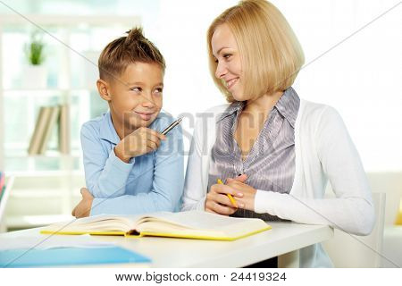 Portrait of pretty tutor and diligent pupil looking at each other while discussing book