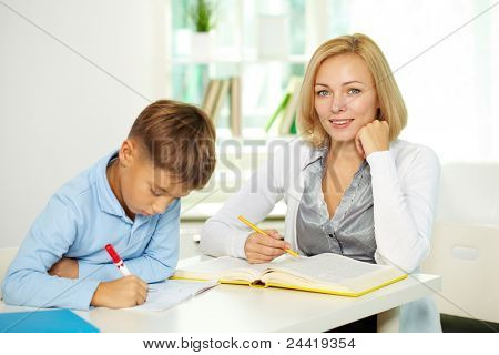 Portrait of pretty tutor looking at camera with diligent pupil making notes near by