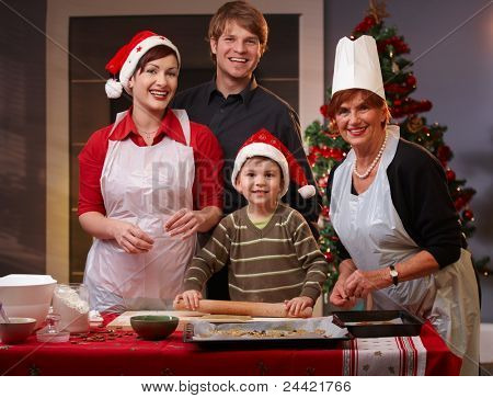 Portrait of happy family of parents, small son and grandmother baking christmas cake together.?