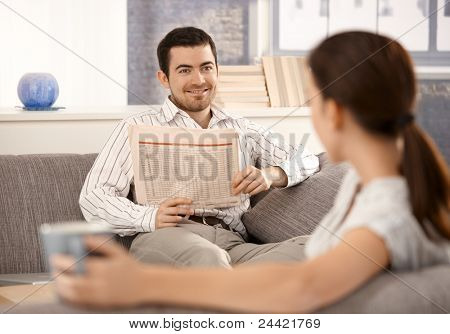 Young couple sitting on sofa in living room, man smiling at woman and reading newspaper, woman drinking tea.?