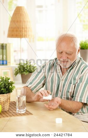 Senior man sitting at table, taking medication with glass of water at home.?
