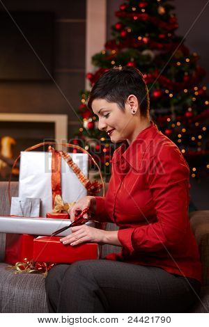 Happy young woman sitting on couch at home, wrapping christmas gifts, smiling. ?