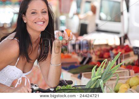 Brunette buying fruit and vegetables at local market