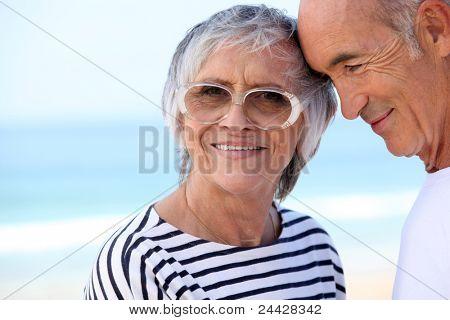 Bejaarde echtpaar op het strand samen