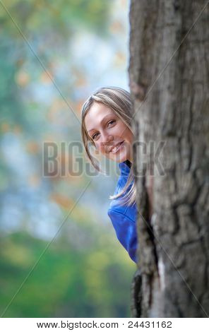 girl stands  of a large oak tree