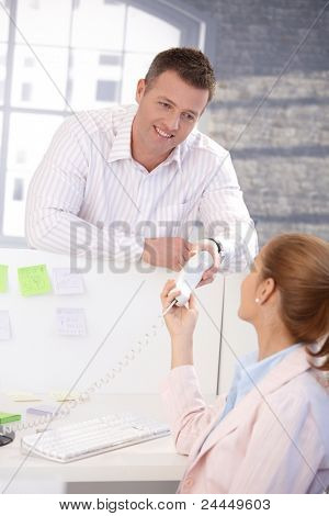Male office worker passing phone to female colleague, smiling.?