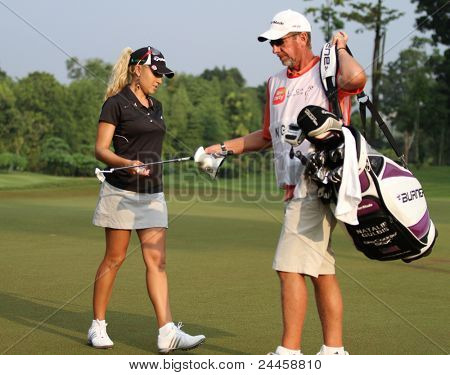 KUALA LUMPUR, MALAYSIA - OCTOBER 16: Natalie Gulbis of the USA takes the putter from her caddiehole #3 at the Sime Darby LPGA Malaysia 2011 golf tournament on Oct 16, 2011 in Kuala Lumpur, Malaysia.