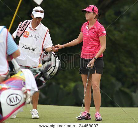 KUALA LUMPUR, MALAYSIA - OCTOBER 16: Paula Creamer of the USA takes the ball from her caddie on day 4 of the Sime Darby LPGA Malaysia 2011 golf tournament on Oct 16, 2011 in Kuala Lumpur, Malaysia.