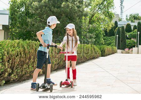 Preschooler Girl And Boy Riding
